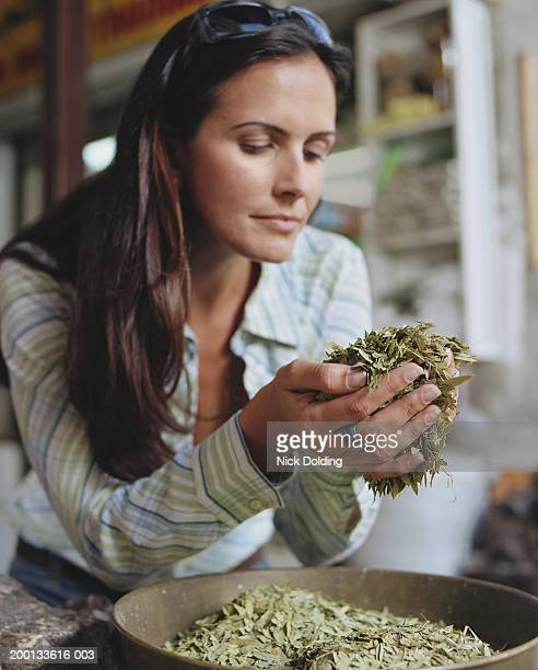 Woman handling spices from dish (focus on hands cupping spices)
