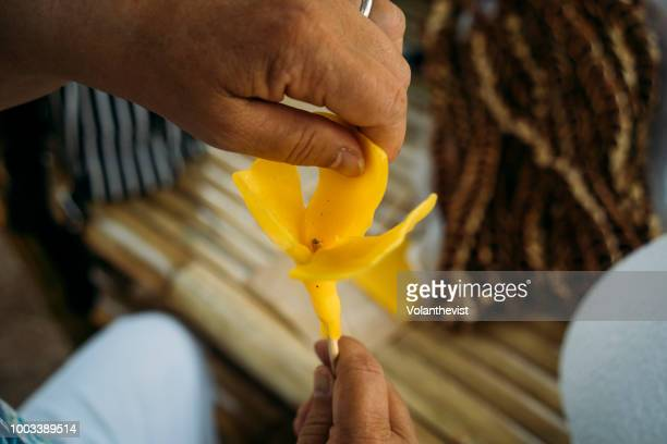 woman handmaking a wax flower shaped candle, chiang mai, thailand - buddhist new year stock pictures, royalty-free photos & images