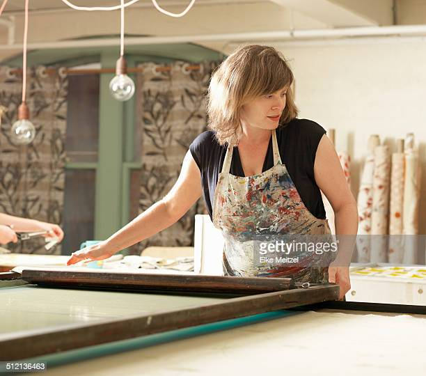 Woman hand-printing textile in workshop