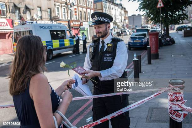 A woman hands a rose to a police officer to lay near the scene of a terror attack in Finsbury Park in the early hours of this morning on June 19 2017...