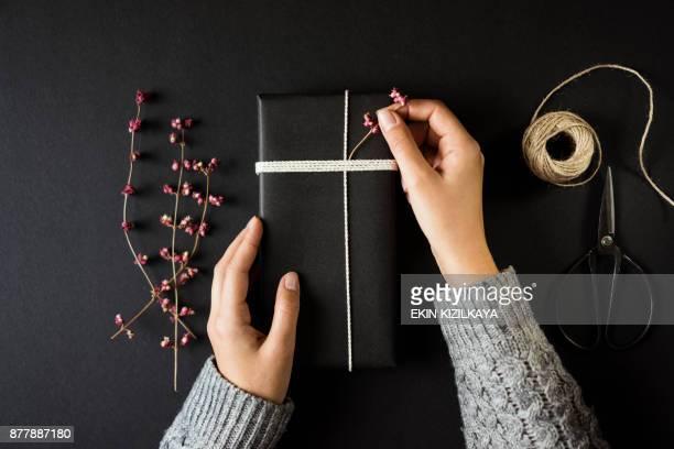 caixa de presente de natal negro de embrulhos para presente de mãos de mulher - table top - fotografias e filmes do acervo