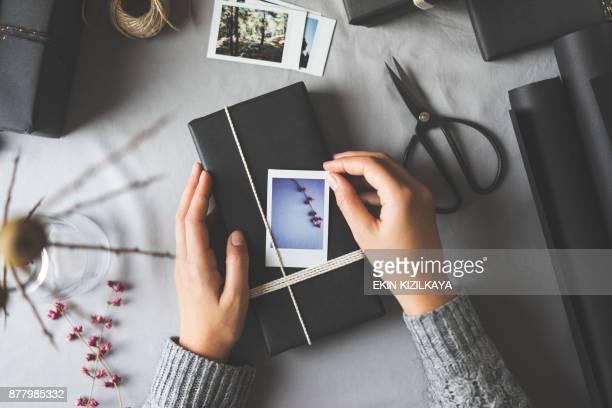 frau hände geschenkpapier weihnachten präsentiert - tischflächen aufnahme stock-fotos und bilder