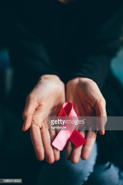 woman hands giving satin pink ribbon - month stock pictures, royalty-free photos & images
