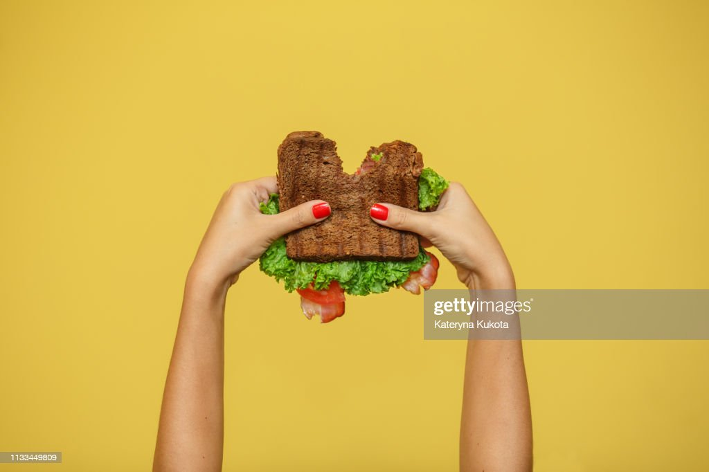Die Hände der Frau halten gebissenes Sandwich auf gelbem Hintergrund. Sandwich-Promotionskonzept. : Stock-Foto