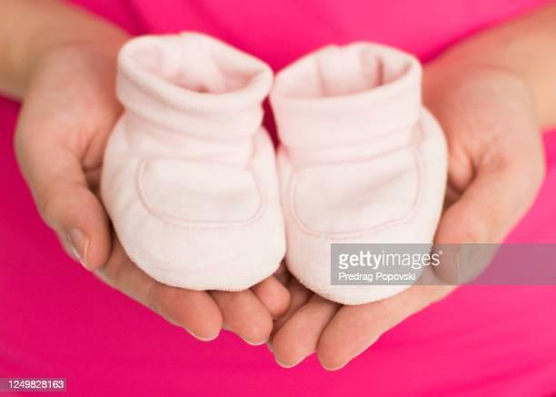 woman hands holding baby shoes - annonce grossesse photos et images de collection