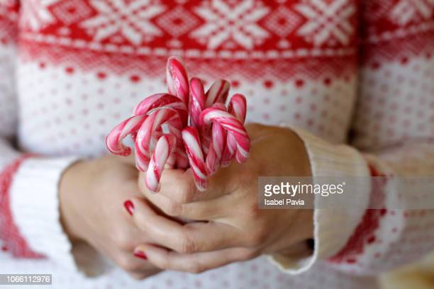 woman hands holding candy canes - candy cane stock pictures, royalty-free photos & images