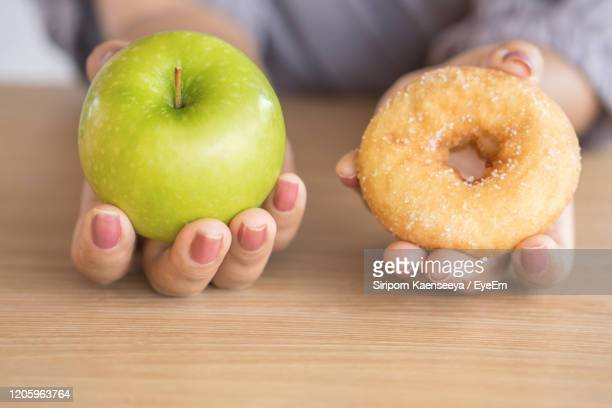 woman hands holding green apple and donut ,healthy or unhealthy eating concept - fat people eating donuts stock pictures, royalty-free photos & images