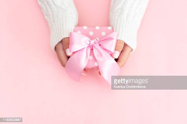 woman hands holding present box with red bow on pastel pink background with multicolored confetti. flat lay style. - pastellfarbig stock-fotos und bilder