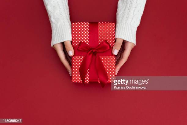 woman hands holding present box with red bow on pastel pink background with multicolored confetti. flat lay style. - cadeau photos et images de collection