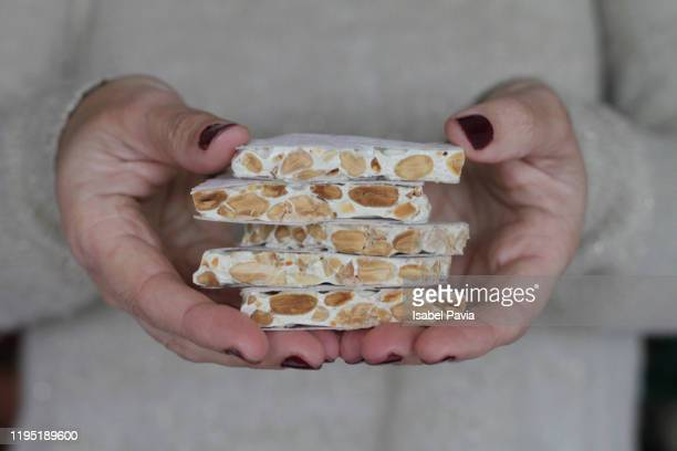 woman hands holding spanish almond nougat or turron de almendras - nougat stock pictures, royalty-free photos & images