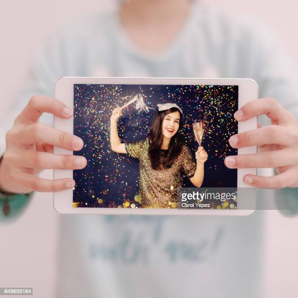 woman hands holding tablet showing a picture of a confetti party girl