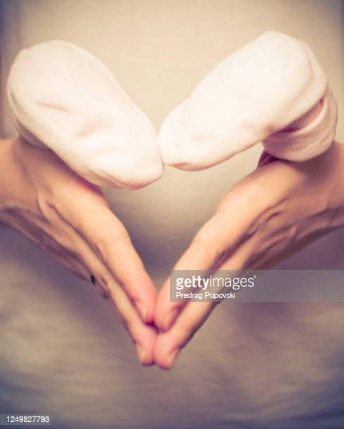 woman hands in heart shape sign holding baby shoes - annonce grossesse photos et images de collection