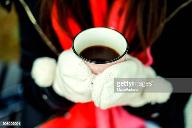 woman hands in white gloves holding a cozy mug with hot cocoa or coffee - mitten stock pictures, royalty-free photos & images