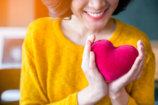 Woman  hands in yellow sweater holding pink heart. 955771066