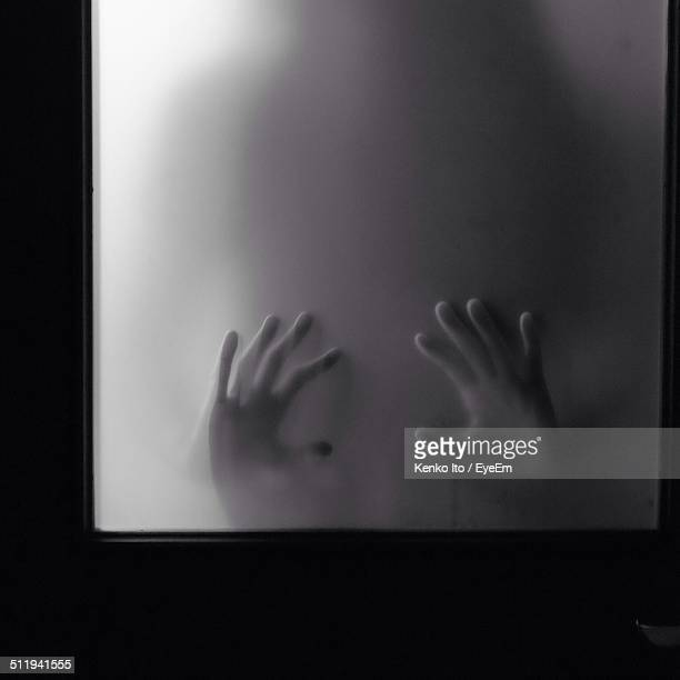 Woman hands looks through frosted glass