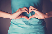 Woman hands making a heart shape on her stomach, healthy bowel degestion, probiotics  for gut health