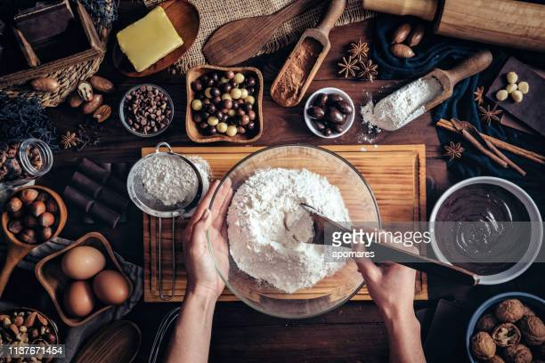woman hands making chocolate mousse and cookies on a wooden table in a rustic kitchen - baked pastry item stock pictures, royalty-free photos & images