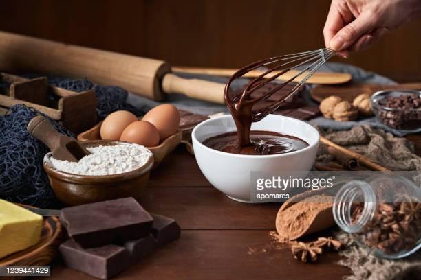 mani da donna che fanno mousse al cioccolato e biscotti su un tavolo di legno in una cucina rustica - cioccolato foto e immagini stock