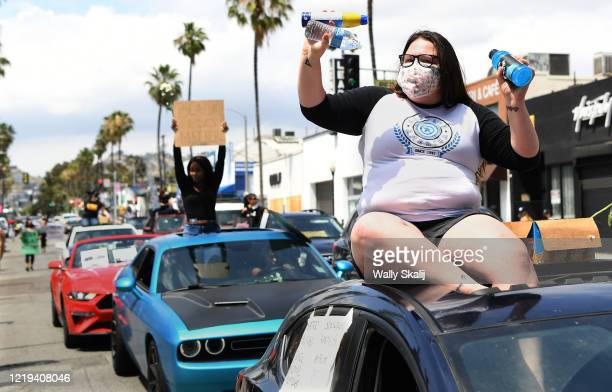 Woman hands out free refreshments to protestors along Fairfax Ave. During a march Saturday. The protest was organzied by the Refuse Fascism group.
