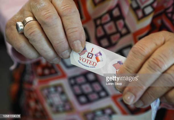 A woman hands out I voted stickers to voters at the Rummel Creek Elementary polling place on November 6 2018 in Houston Texas Voters visited polling...