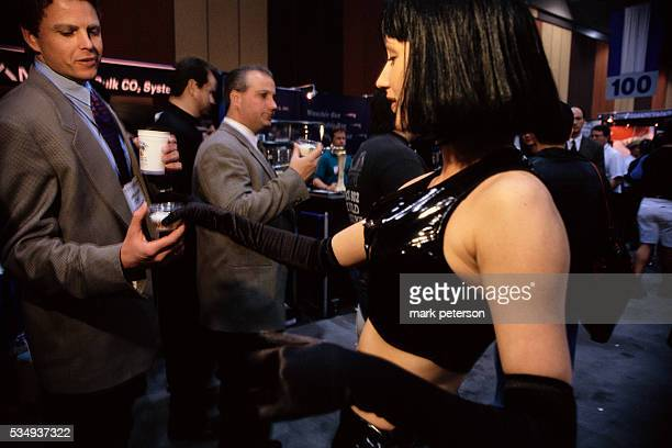 A woman hands out products at the Nightclub and Bar Convention and Trade Show held at the Las Vegas Convention Center