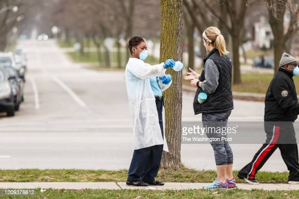 Woman hands out surgical masks to people standing in line to vote in Wisconsins spring primary election on Tuesday, April 7, 2020 at Riverside High...