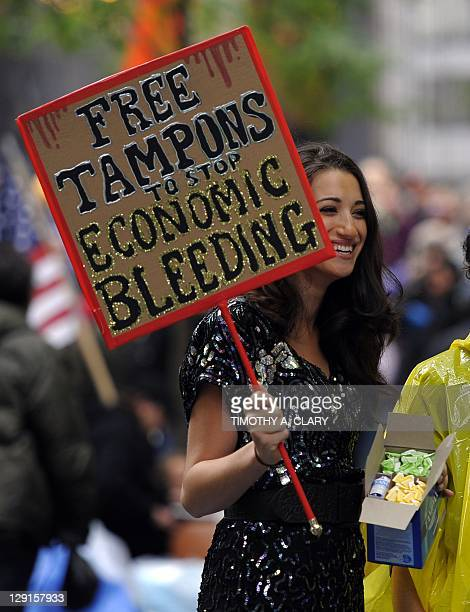 A woman hands out tampons to demonstrators with 'Occupy Wall Street' protest at Zuccotti Park in New York before they start cleaning up their...