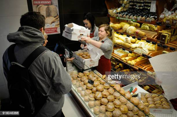 A woman hands over a box full of paczki or Polish donuts on Tlusty Czwartek on February 8 2018 Tlusty Czwartek or Fat Thursday is the last Thursday...