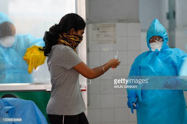 Woman hands over a her sample at a COVID-19 testing and sample collection centre during a government-imposed nationwide lockdown as a preventive...