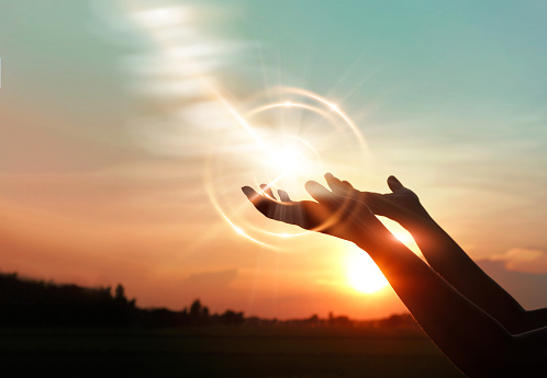 Woman hands praying for blessing from god on sunset background 1127245421