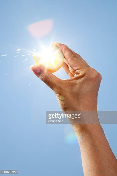 Woman hands squeezing a lemon slice
