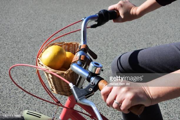 woman hands steering a handlebar of a bicycle - rafael ben ari stock-fotos und bilder