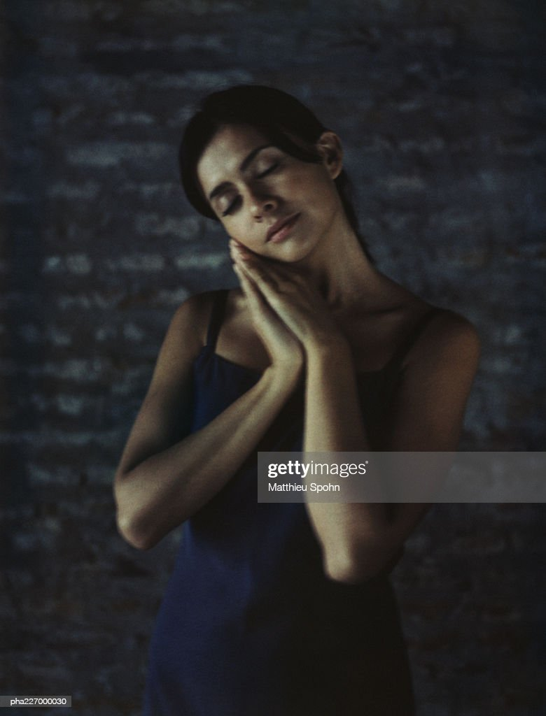 Woman, hands together, eyes closed, portrait. : Stockfoto