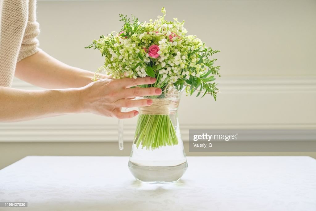 Woman hands with bouquet of flowers in vase on table : Stock Photo