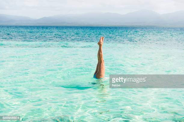 Woman handstand in turquoise sea