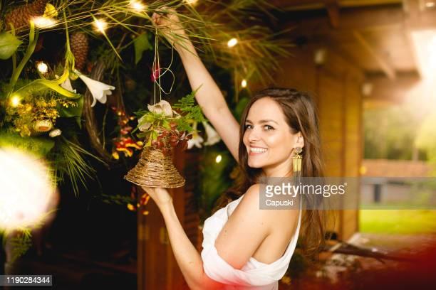 mulher que pendura um ornamento de sino para a decoração do natal - metereologia - fotografias e filmes do acervo