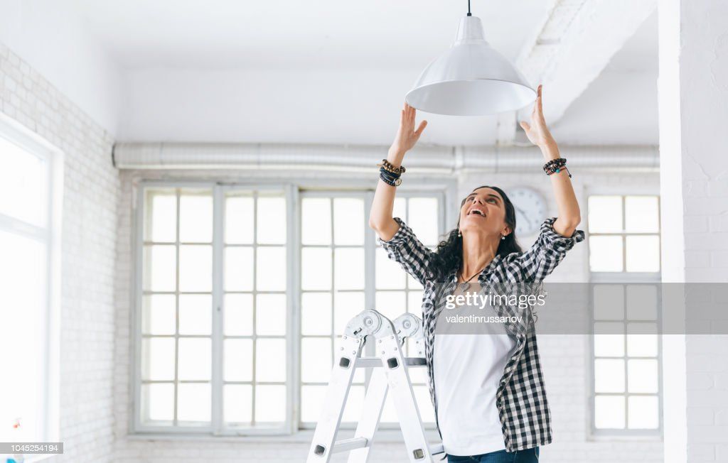 Woman hanging a lamp in new home Property Services. New Home. : Stock Photo