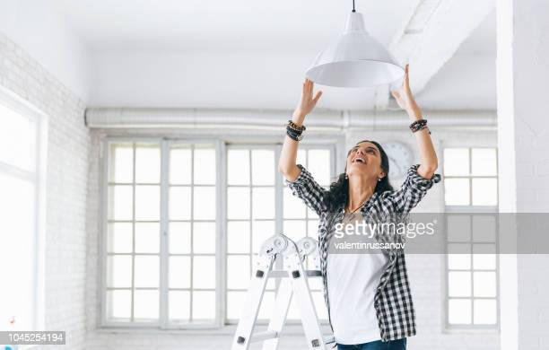 woman hanging a lamp in new home property services. new home. - ornato foto e immagini stock