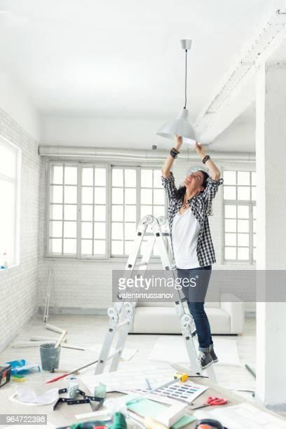 mulher uma lâmpada em casa nova propriedade serviços de suspensão. nova casa. - electric lamp - fotografias e filmes do acervo