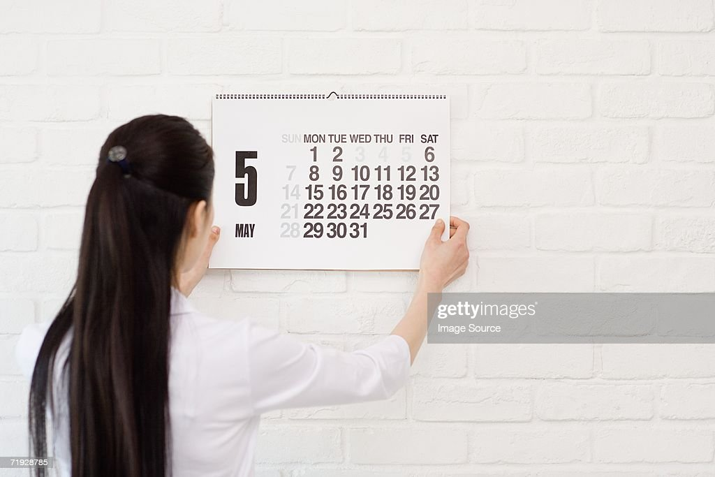 Woman hanging calendar on wall : Stock Photo