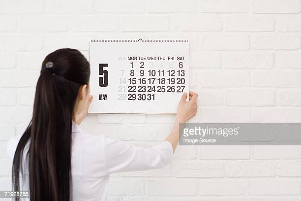 Woman hanging calendar on wall
