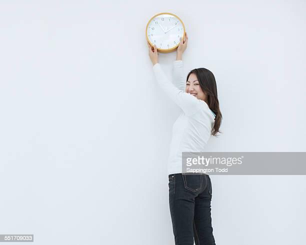 Woman Hanging Clock On Wall