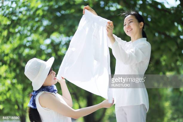 woman hanging clothes with daughter - 洗濯 ストックフォトと画像