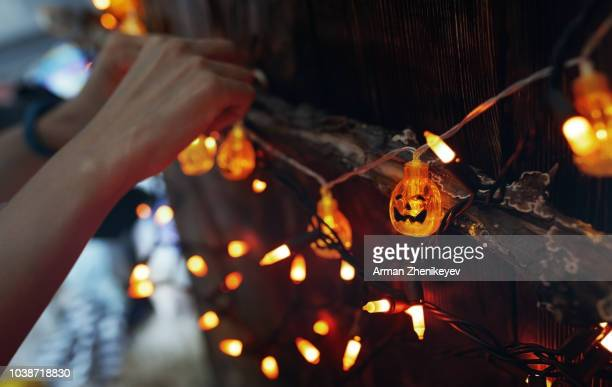 woman hanging decorative eletric light with pumpkins. halloween theme - happy halloween stock photos and pictures