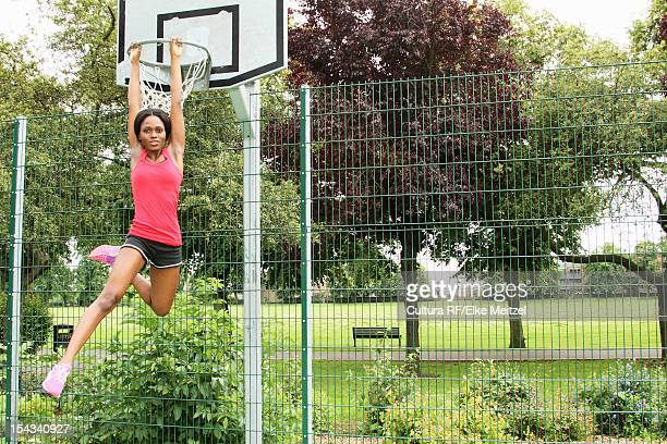Woman hanging from basketball net