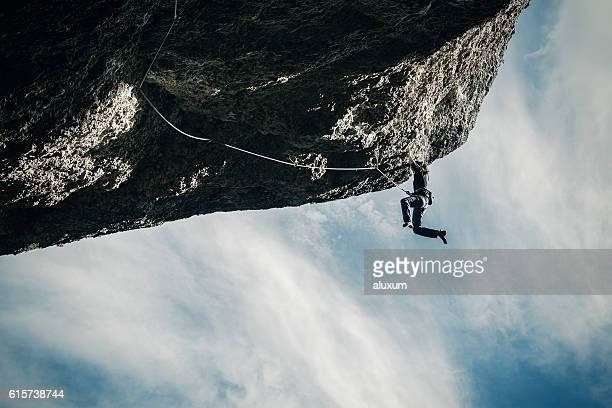 Woman hanging from cliff