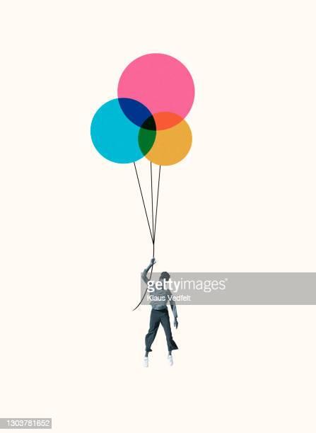 woman hanging from colorful helium balloons - compuesto digital fotografías e imágenes de stock