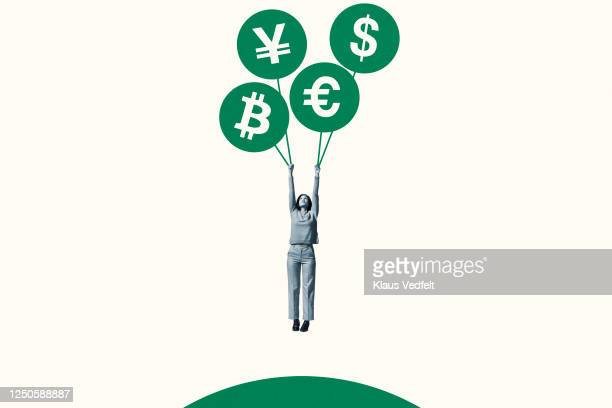 woman hanging from green currency symbol balloons - currency exchange stock pictures, royalty-free photos & images