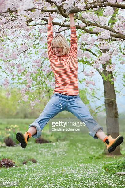 woman hanging from tree branch