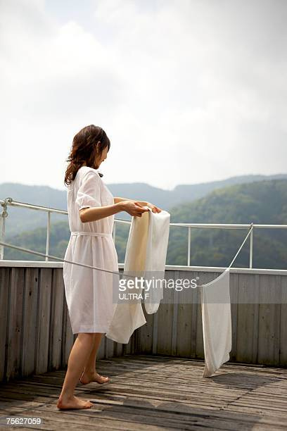 Woman hanging laundry on clothes line on wooden patio